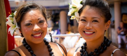 Two women smiling with flowers in their hair