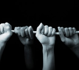 The hands of two people grasping a rope