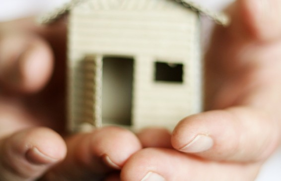 two people holding a miniature house in their hands