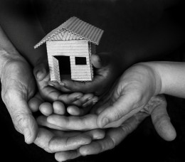 Three people's hands holding a miniature house
