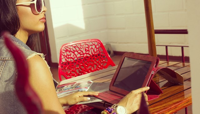 Woman wearing sunglasses sitting at a sunny table outside using tablet