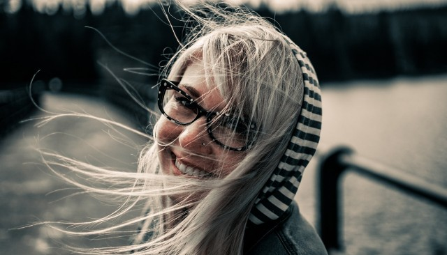 Woman with glasses smiling and hair blowing in the wind