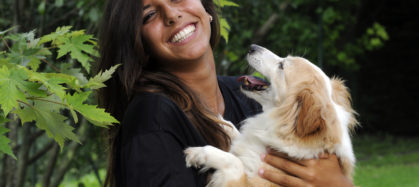 Woman holding her dog and smiling