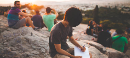 People hiking and boy writing in notebook
