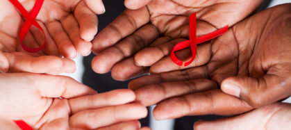 group of multiracial people holding red ribbon for AIDS HIV awareness