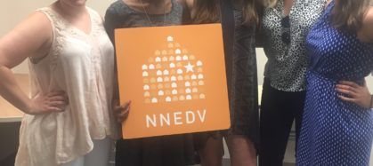 Photograph of NNEDV staff member Lysaundra Campbell, posing with summer 2016 interns in the office. They are holding an NNEDV sign.