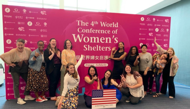 NNEDV staff poses in front of the the Fourth Global Conference of Women's Shelters sign.