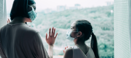 Woman wearing mask with hand on window looks down at female child, also wearing mask